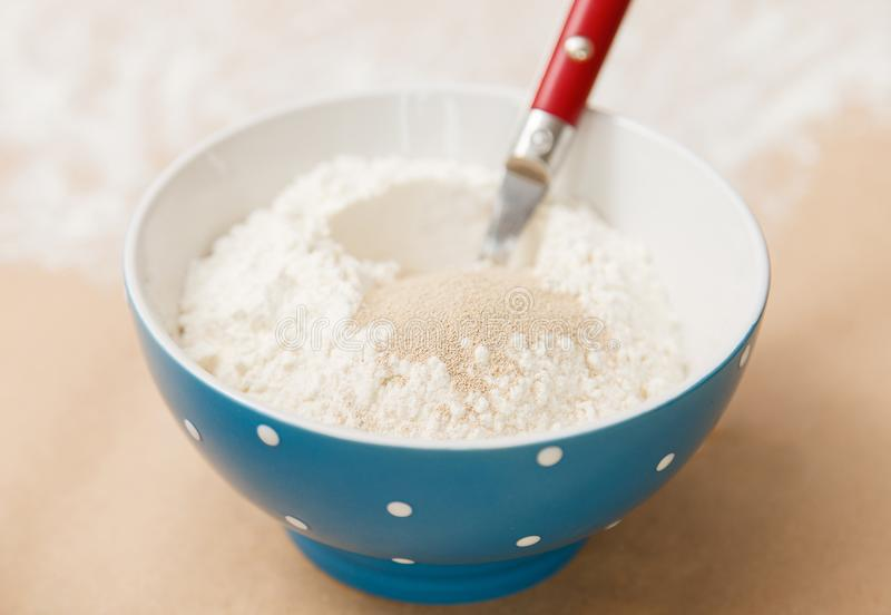 Hinzufügen der Hefe dem Mehl stockfoto