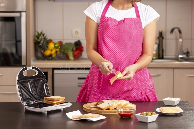 Hinzufügen der Käsescheibe auf einem Sandwich stockbilder