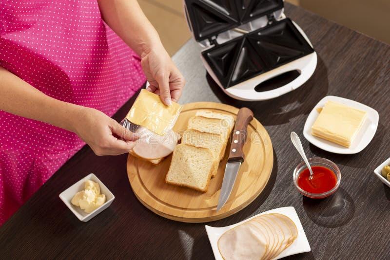 Hinzufügen der Käsescheibe dem Sandwich lizenzfreies stockfoto