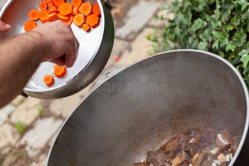 Hinzufügen der Karotte in einem großen Kessel mit Lamm lizenzfreie stockfotos