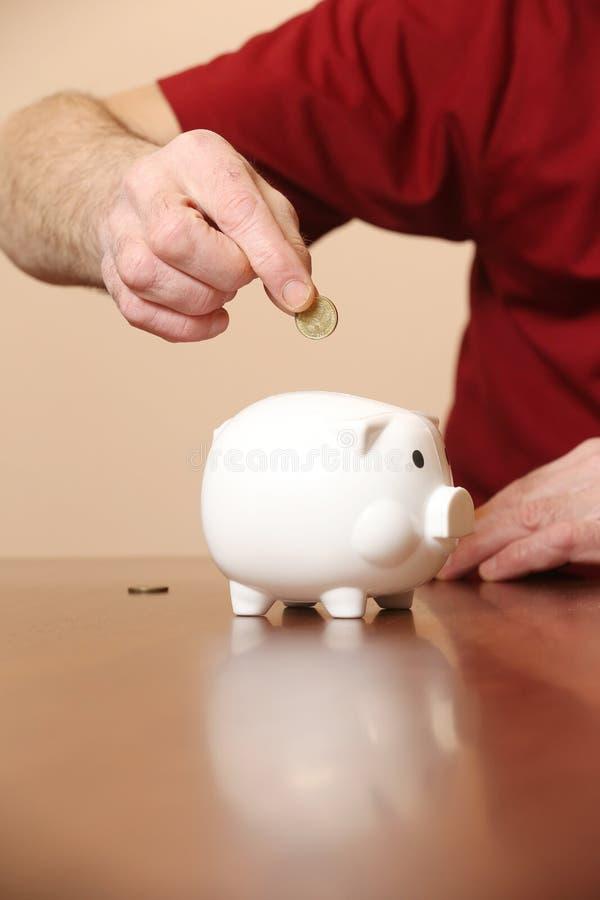 Hinzufügen der Münze im Sparschwein lizenzfreie stockfotografie