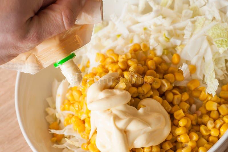 Hinzufügen der Mayonnaise einem Salat des in Büchsen konservierten Mais und des Weißkohls lizenzfreie stockbilder