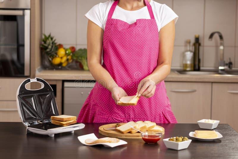 Hinzufügen der Salami auf einem Sandwich stockfotos
