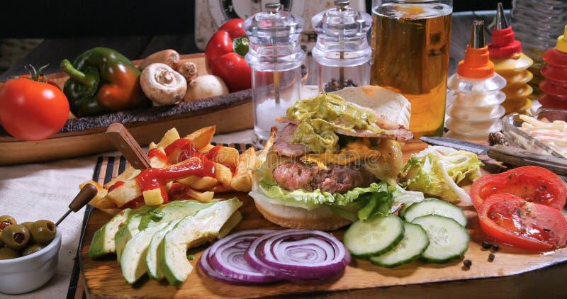 Hinzufügen des Guacamolen über einem cheesburger mit Bier und Pommes-Frites stockfotos