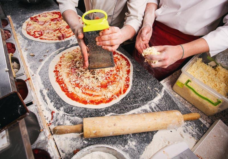 Hinzufügen des Käses Pizza Stadien des Kochens der Pizza stockbilder