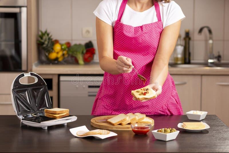Hinzufügen des Ketschups auf einem Sandwich lizenzfreies stockbild