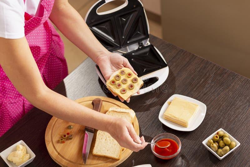 Hinzufügen des Ketschups auf einem Sandwich lizenzfreies stockfoto