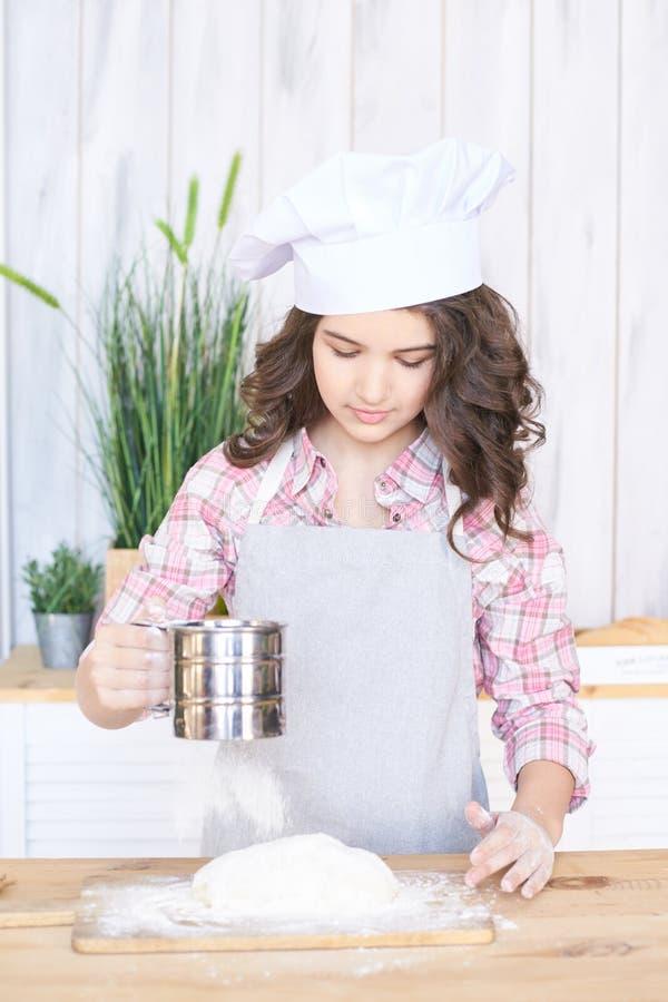 Hinzufügen des Mehls Prüfen Sie Vorbereitung Mädchen in der Küche Wenig kochen stockfotos