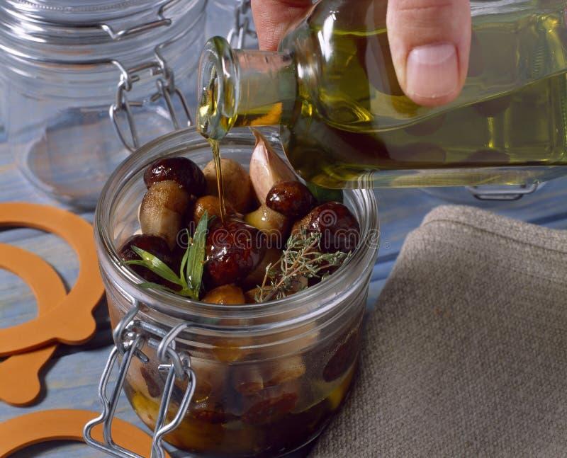 Hinzufügen des Olivenöls stockbilder