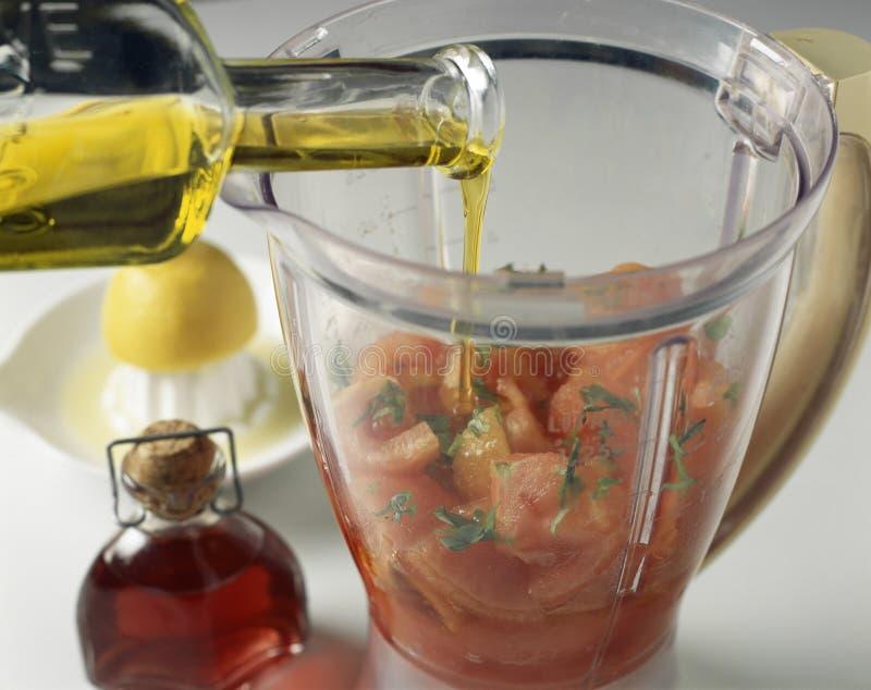Hinzufügen des Olivenöls lizenzfreie stockfotografie