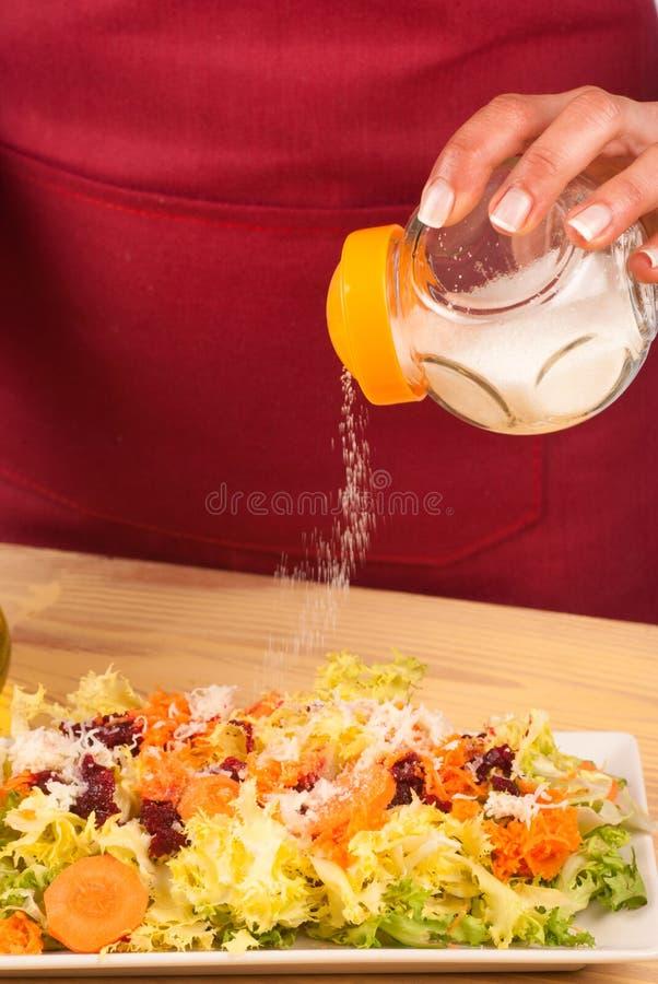 Hinzufügen des Salzes stockfotos