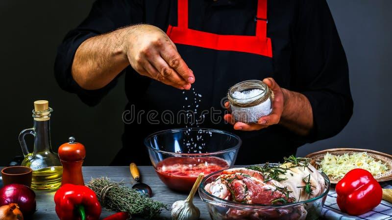 Hinzufügen des Salzes durch Chefhände Kochen des bayerischen Schweinefleischknöchels mit Sauerkraut, scharfer Chili-Sauce und Bie stockfotos