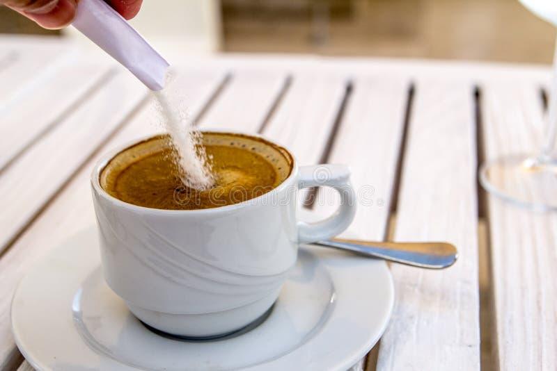Hinzufügen des Zuckers einer Cappuccinoschale auf einem weißen Holztisch an einem sonnigen Sommertag lizenzfreies stockbild