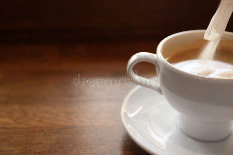 Hinzufügen des Zuckers frischem aromatischem Kaffee auf Tabelle lizenzfreie stockfotografie