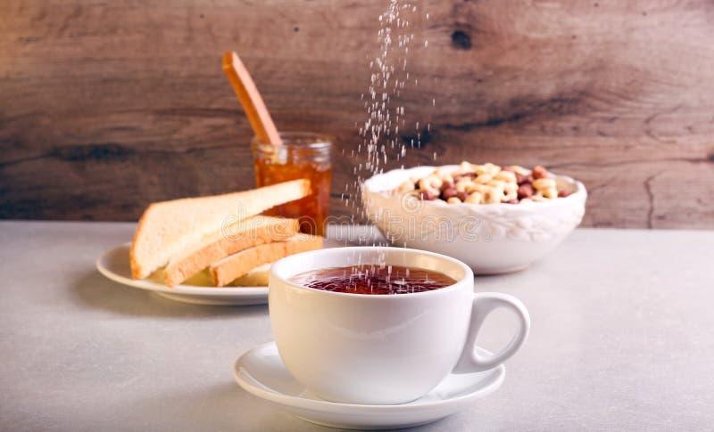 Hinzufügen des Zuckers in Tee in einer Schale stockfoto