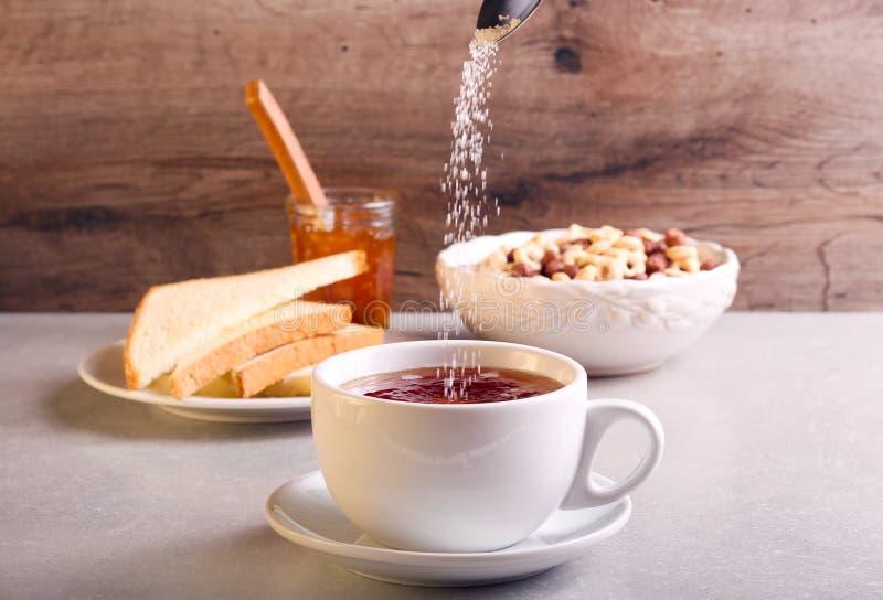 Hinzufügen des Zuckers in Tee in einer Schale lizenzfreies stockbild