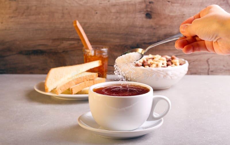 Hinzufügen des Zuckers in Tee in einer Schale lizenzfreies stockfoto