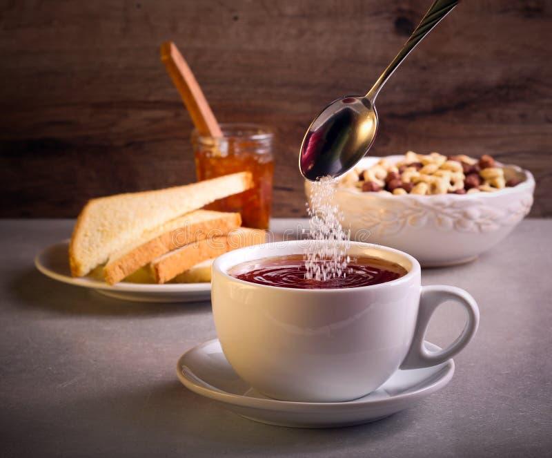 Hinzufügen des Zuckers in Tee in einer Schale lizenzfreie stockfotos