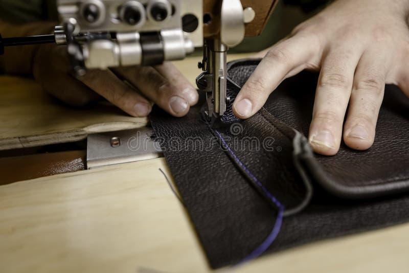 Hinzufügen einer ledernen Tasche auf einer Handelsnähmaschine lizenzfreie stockbilder