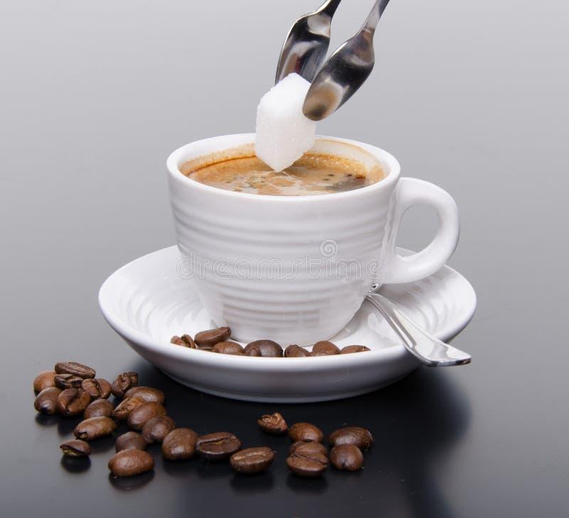 Hinzufügen eines Zuckers in einem Kaffee stockfotografie