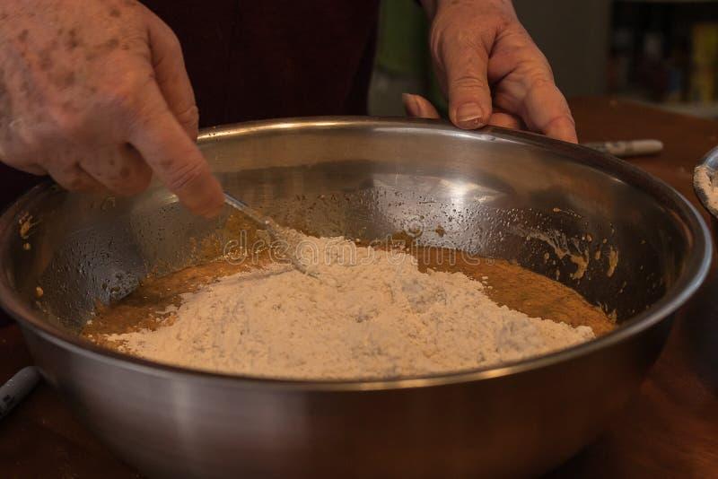 Hinzufügen und Mischen im Mehl in eine Schüssel stockfotografie