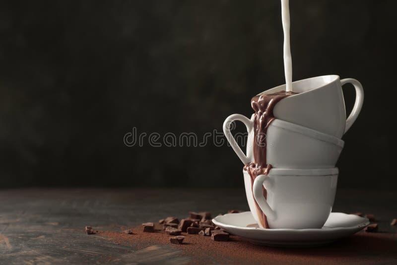 Hinzufügen von Milch geschmackvoller heißer Schokolade auf Tabelle lizenzfreie stockbilder