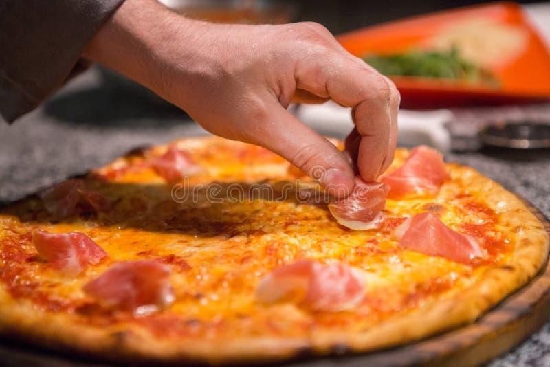 Hinzufügen von Prosciutto Pizza lizenzfreie stockbilder