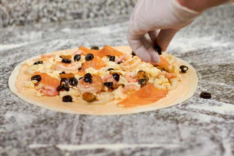 Hinzufügen von schwarzen Oliven Pizza stockbild