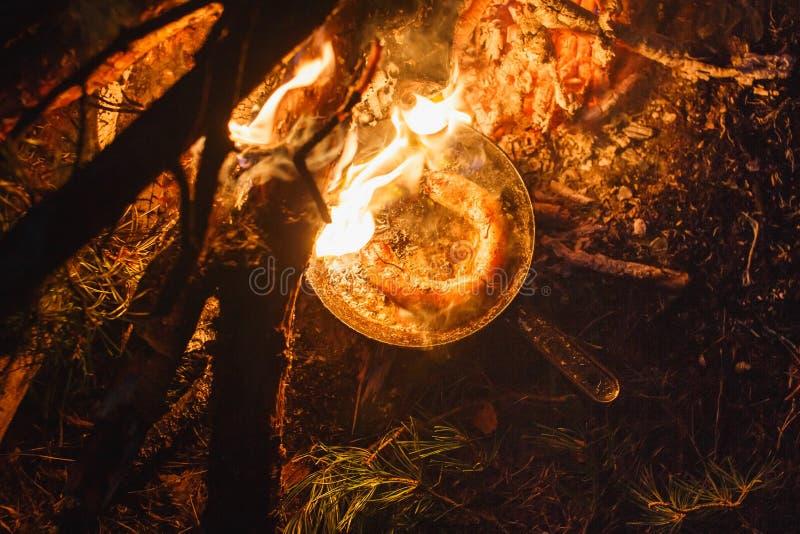 Hinzufügen von Würsten in einer Wanne auf einem Feuer im Nachtwald lizenzfreie stockfotografie