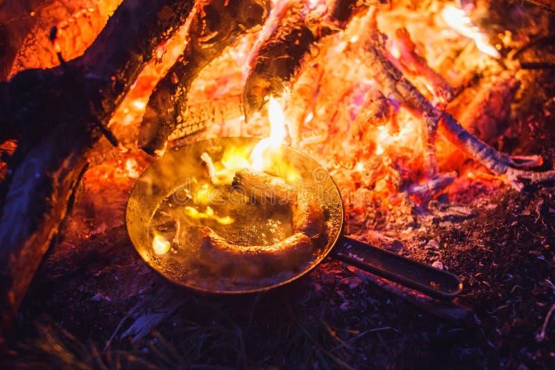 Hinzufügen von Würsten in einer Wanne auf einem Feuer im Nachtwald lizenzfreies stockbild