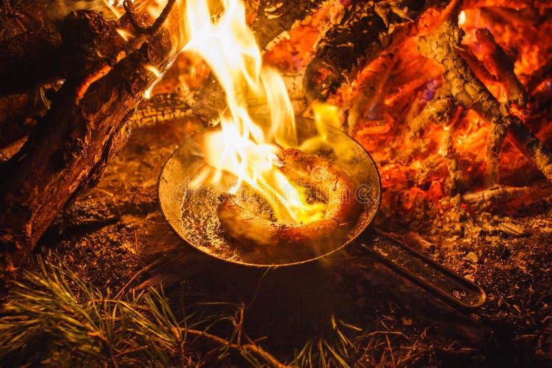 Hinzufügen von Würsten in einer Wanne auf einem Feuer im Nachtwald stockfotografie