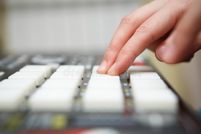Hip hop beat maker producing new beats with midi controller device in home studio. Beat maker producing new track with professional midi controller device in stock photos