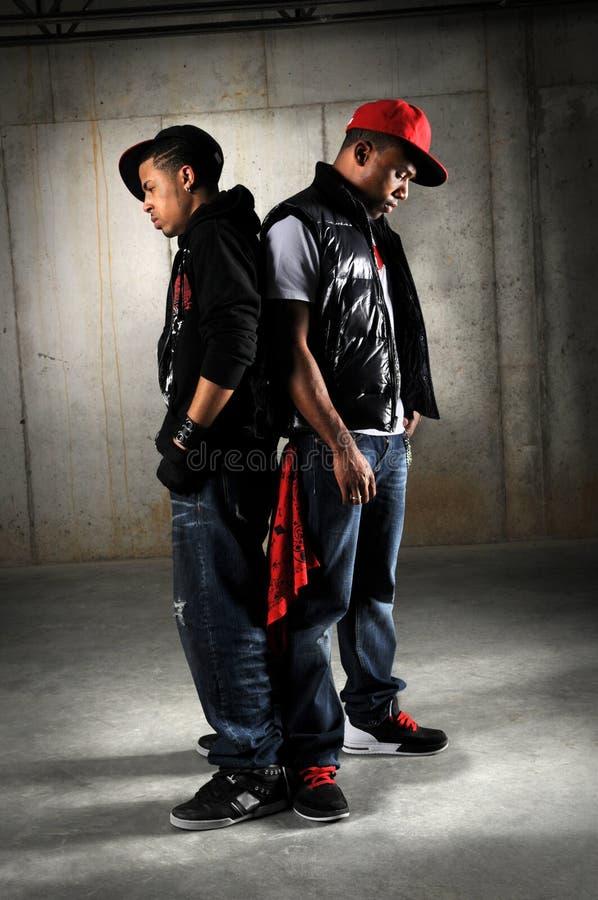 Hip Hop Dancers Posing. African American hip hop dancers performing over industrial background stock image