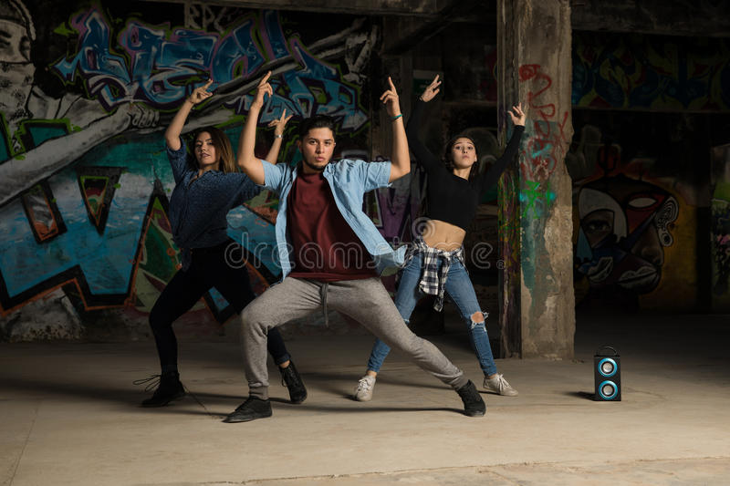 Hip hop dancers practicing a routine. Full length view of a group of three hip hop dancers practicing a dance routine in an abandoned building royalty free stock photo