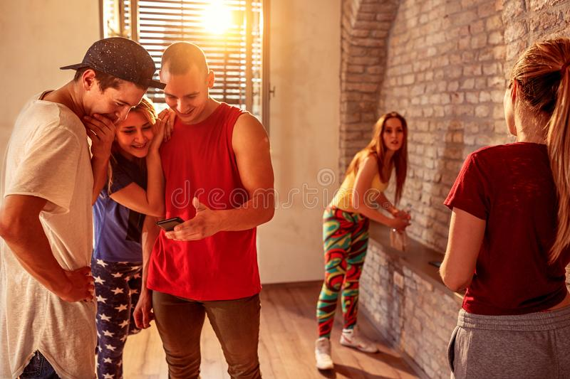 Hip hop dancers rest during a break and communicate with each ot. Hip hop modern dancers rest during a break and communicate with each other and use mobile phone stock photos