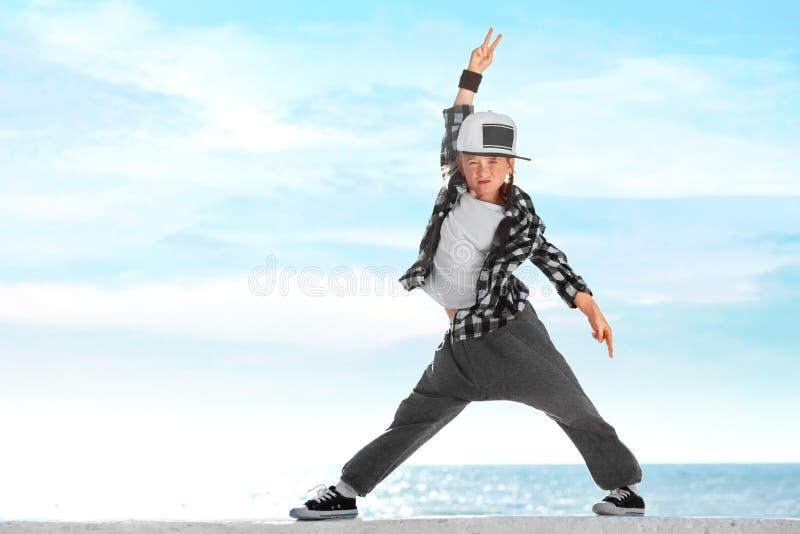 Hip-hop felice di dancing della bambina sul fondo del cielo blu immagini stock libere da diritti