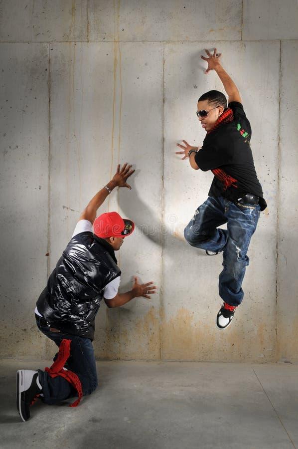 Hip Hop Men Performing. African American hip hop dancers performing against wall stock photo
