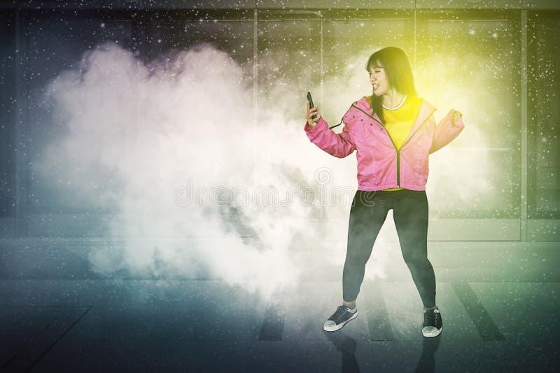 Hip-Hop-Tänzer tanzt mit Telefon im Bahnhof lizenzfreie stockfotos
