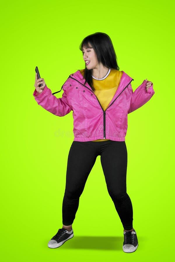 Hip-Hop-Tänzertanzen mit Telefon auf Studio lizenzfreie stockfotografie