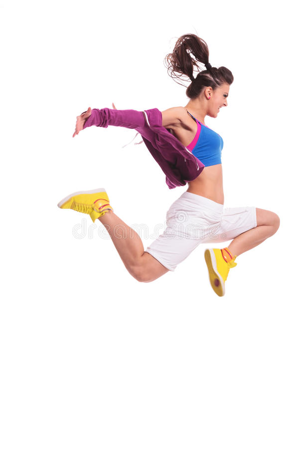 Hip hop woman dancer jumping. Side view of a young woman hip hop dancer jumping with a violent expresion on her face and with arms extended stock image