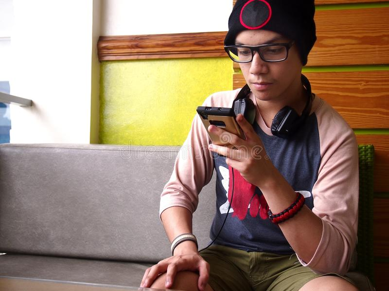 Hip male teenager using a smartphone royalty free stock photography