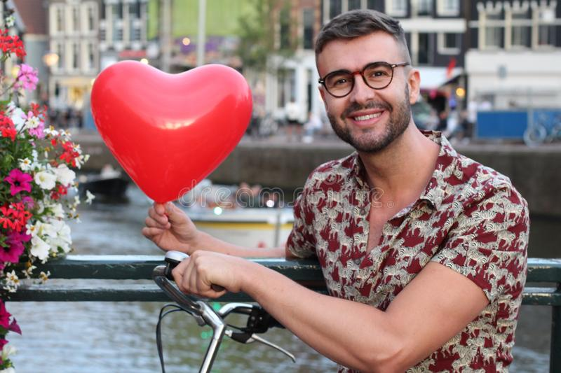 Hip man holding heart shaped balloon in Amsterdam stock images