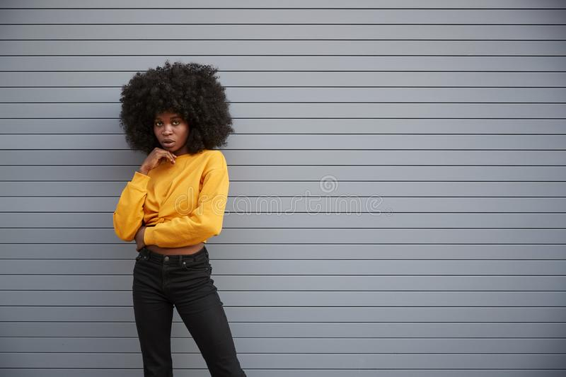 Hip young African American woman standing against grey security shutters, head on hand, looking to camera royalty free stock images