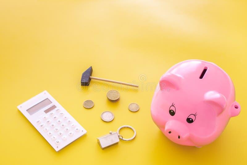 hipoteca Ahorros para la casa de la compra Moneybox en la forma del cerdo cerca del llavero en la forma del coche, monedas, calcu foto de archivo