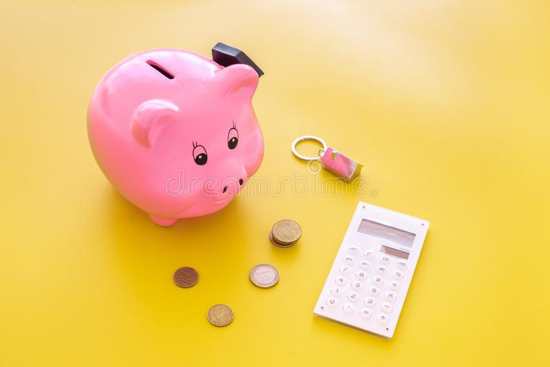 hipoteca Ahorros para la casa de la compra Moneybox en la forma del cerdo cerca del llavero en la forma del coche, monedas, calcu fotografía de archivo