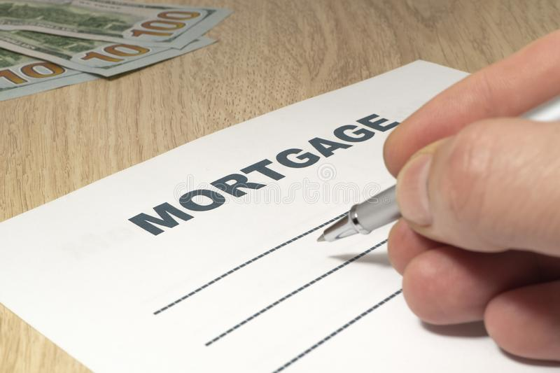 Hipoteca com uma pena, um dinheiro e uma mão na tabela imagens de stock royalty free
