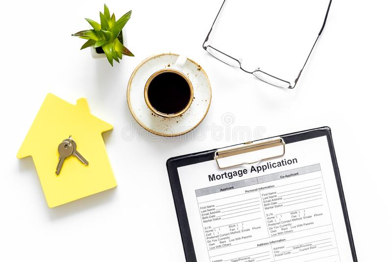 Hipoteka domowa z aplikacją, kawą, okularami, zabawką domową, klawiszami na biurku białego bankiera zdjęcie royalty free