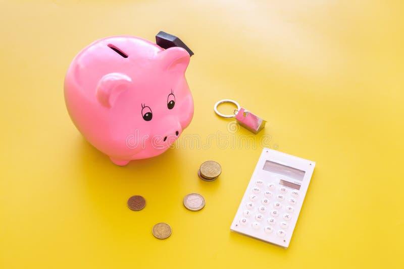 hipoteka Savings dla zakupu domu Moneybox w kształcie świniowaty pobliski keychain w kształcie samochód, monety, kalkulator na ko fotografia stock