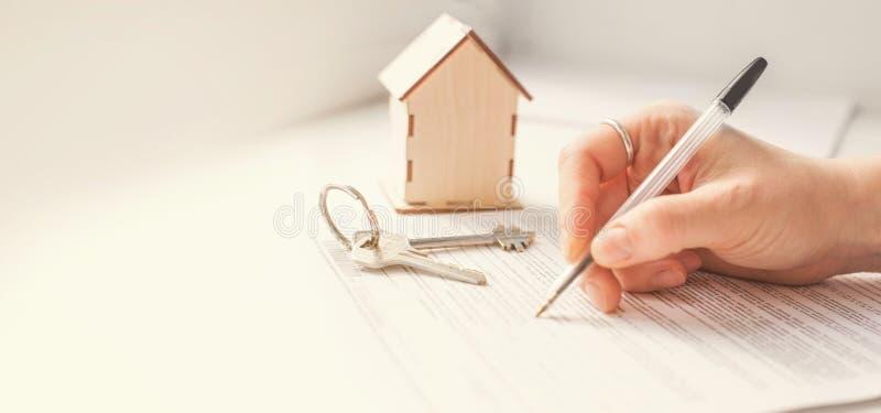 Hipoteki i budynek mieszkalny czynsz Wpisuje, dom i ręka która podpisuje dokumenty fotografia stock