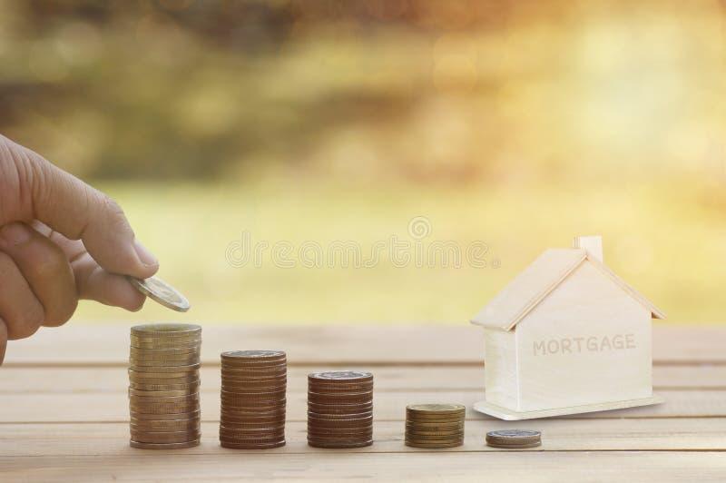 Hipoteque el concepto, dinero apilado mano en monedas con la casa de madera en la tabla de madera, concepto como comprando, consi fotos de archivo libres de regalías